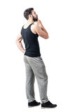 Side view of man in tank top and sweatpants looking up with hand on chin Royalty Free Stock Image