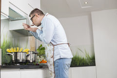 Side view of man tasting food while cooking in kitchen Stock Photos