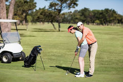 Side view of man teaching woman to play golf Royalty Free Stock Image