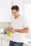 Side view of a man text messaging in kitchen Stock Images