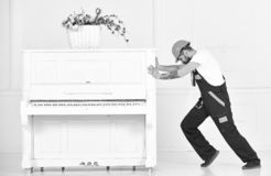 Side view man trying to relocate heavy piano isolated on white background. Strong man building muscles at work. Side view bearded man trying to relocate heavy royalty free stock photos