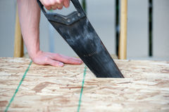 Side view of a man using a hand saw with motion blur. Of the saw Royalty Free Stock Images