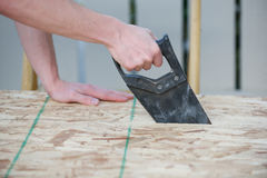Side view of a man using a hand saw. With particle board wood Stock Photo