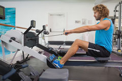 Side view of man using resistance band in gym Stock Photos