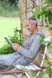 Side view of man using tablet in garden Royalty Free Stock Photos