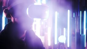 Man using VR headset in mist with neon lights. Side view man in VR headset moving hands with colored motion controllers. Crop gamer in dark space with fog on stock video footage