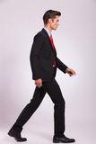 Side view of man walking & looking away Stock Photo
