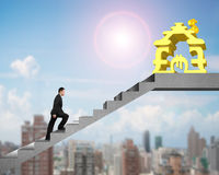 Side view man walking on stairs to money stacking house Royalty Free Stock Photo
