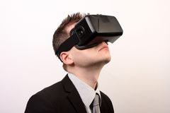 Side view of a man wearing a VR Virtual reality Oculus Rift 3D headset, looking upwards in a black official suit Stock Image
