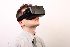 Side view of a man wearing a VR Virtual reality Oculus Rift 3D headset, looking upwards in a formal shirt and tie Royalty Free Stock Photos