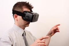 Side view of a man wearing a VR Virtual reality Oculus Rift 3D headset, touching or pointing at something with his hands Stock Image