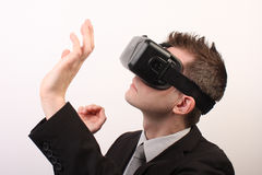 Side view of a man wearing a VR Virtual reality Oculus Rift 3D headset, touching something with his hands, exploring royalty free stock photo