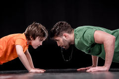 Side view of man with whistle and boy doing push ups and looking at each other stock images