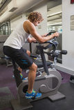 Side view of man working out on exercise bike at gym Stock Image