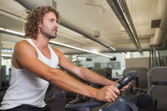 Side view of man working out on exercise bike at gym Stock Photos