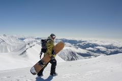 Side view manful snowboarder walking with the snowboard in the m royalty free stock photos