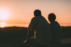 Side view a married couple a silhouette sitting on a bench. Stock Photography