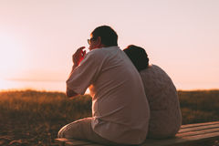Side view a married couple a silhouette sitting on a bench. Royalty Free Stock Images