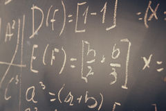 Side view of math formulas and calculation written over chalkboard. selective focus. Royalty Free Stock Photos