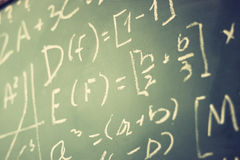 Side view of math formulas and calculation written over chalkboard. selective focus. Stock Images