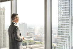 Side view of mature businessman looking through office window Royalty Free Stock Images