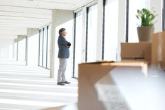 Side view of mature businessman looking through window in new office Royalty Free Stock Photo