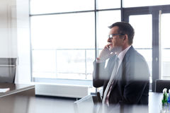 Side view of mature businessman talking on mobile phone at office Royalty Free Stock Image