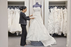 Side view of a mature employee adjusting elegant wedding dress in bridal store Stock Photography