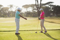 Side view of mature male golf player teaching woman. Side view of mature male golf player teaching women while standing on field Royalty Free Stock Image
