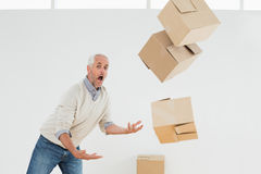 Side view of a mature man with falling boxes Royalty Free Stock Image