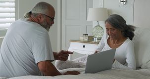 Mature couple at home. Side view of a mature mixed race couple using a laptop computer sitting on a bed at home stock video