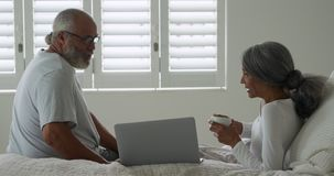 Mature couple at home. Side view of a mature mixed race couple using a laptop computer and talking in their bedroom at home stock footage