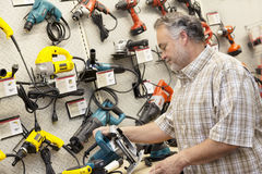 Side view of mature salesperson looking at electric saw Royalty Free Stock Images