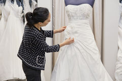 Side view of mature woman adjusting bridal dress in boutique Stock Photo