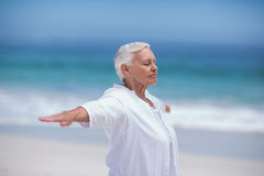 Side view of mature woman posing with outstretched arms Stock Images