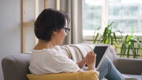 Side view of mature woman is using tablet sitting on sofa at home. Side view of mature woman is using tablet sitting on sofa at home, elderly brunette is stock video