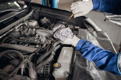 Side view of mechanic checking motor oil in a car with open hood Royalty Free Stock Images