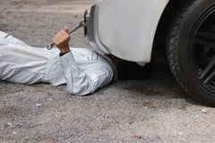 Side view of mechanic in white uniform lying down and fixing under car. Auto repair service. Side view of mechanic in white uniform lying down and fixing under stock photo