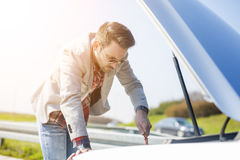 Side view of men checking motor oil Royalty Free Stock Photo