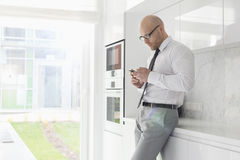 Side view of mid adult businessman using cell phone at home Stock Image