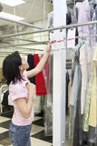 Side view of mid adult woman looking at clothing rack Royalty Free Stock Photos