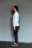 Side view of mid aged actor in casual clothes. Side view of brutal man on grey background Royalty Free Stock Images