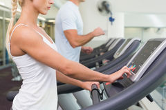 Side view mid section of couple running on treadmills at gym Royalty Free Stock Images