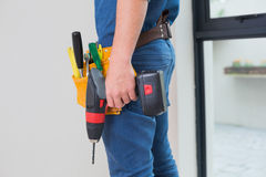 Side view mid section of a handyman with drill and toolbelt Stock Photos