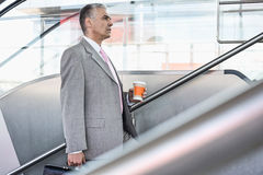 Side view of middle aged businessman with coffee cup walking up stairs in railroad station Stock Photo
