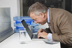 Side view of middle-aged businessman using laptop at desk in office Stock Photos