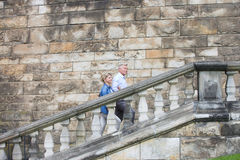 Side view of middle-aged couple climbing steps outside old building stock photography