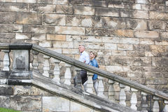 Side view of middle-aged couple climbing steps outside old building royalty free stock images
