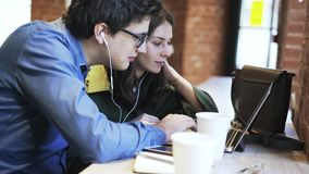 Side view of a millennial couple using headphones together in a cafe stock video