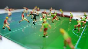 Side view of miniature toys figurines football soccer players on a computer pad.  stock video